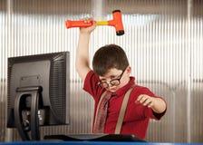 Nerdy boy smashing his computer. Nerdy young boy smashing his computer with a hammer Stock Image