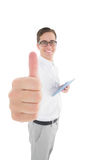 Nerdy businessman holding his digital tablet showing thumbs up Stock Photography