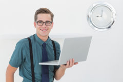 Nerdy businessman holding laptop smiling at camera Stock Photo