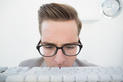 Nerdy businessman looking at keyboard Royalty Free Stock Image