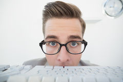 Nerdy businessman looking at keyboard Stock Images
