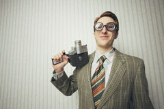 Nerdy businessman with old fashioned cine camera Stock Images