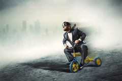 Nerdy businessman riding a small bicycle Stock Images