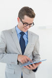 Nerdy businessman using his tablet pc Stock Photo