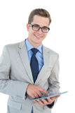 Nerdy businessman using his tablet pc Stock Photography
