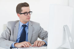 Nerdy businessman working on computer Stock Photo