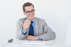 Nerdy businessman working on computer pointing at camera Stock Images