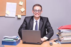 Nerdy businessman working on a laptop. In the office stock photography