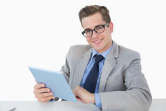 Nerdy businessman working on tablet pc Royalty Free Stock Images