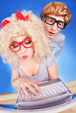 Nerdy couple. Funny guy is spying on girlfriend she is using laptop computer Royalty Free Stock Photos