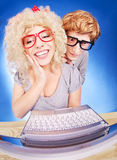 Nerdy couple. Funny guy is spying on girlfriend she is using laptop computer Stock Images