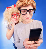 Nerdy couple. Girl is spying on boyfriend he is using a smart phone Stock Photos