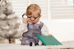 Nerdy fjärdpojke som läser en bok arkivbild