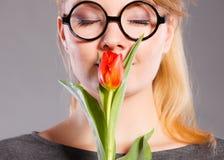 Nerdy flicka som luktar blomman Arkivfoton