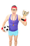 Nerdy football player holding a trophy Stock Photo