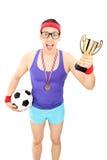 Nerdy fotbollsspelare som rymmer en trofé arkivfoto