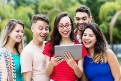 Nerdy french female student with tablet computer and group of international students. Outdoors in summer in the city royalty free stock images
