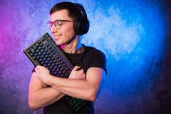 Nerdy gamer wearing headset with microphone hugs keyboard. Game addiction concept stock photos