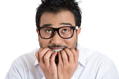 A nerdy geek looking young student with big black glasses, biting nails in anxiety Stock Photography