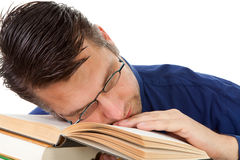 Nerdy geek valt in slaap op boeken Stock Foto