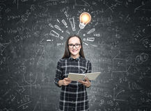 Nerdy girl, bulb and exclamation marks. Portrait of a smiling nerdy girl wearing glasses and a black checkered shirt and holding a book while standing near a Royalty Free Stock Photos