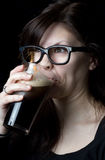 Nerdy girl drinking a beer Royalty Free Stock Image
