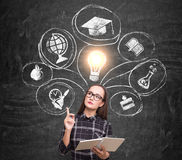 Nerdy girl and education choice on blackboard. Portrait of a nerdy girl holding a book and wearing glasses while standing near a blackboard with education choice Royalty Free Stock Photo