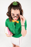 Nerdy girl holding spectacles looking up. Stock Image
