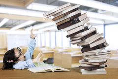 Nerdy girl with pile of falling books Royalty Free Stock Photo