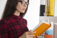 Nerdy girl is reading a sci-fi book Royalty Free Stock Photo