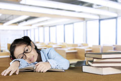Nerdy girl sleeping with a pile of books Royalty Free Stock Images