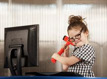 Nerdy girl smashing her computer. Nerdy young girl smashing her computer with a hammer Royalty Free Stock Images