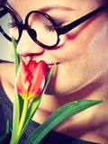 Nerdy girl smelling flower. Royalty Free Stock Photography