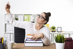 A nerdy girl is taking a selfie with a stack of books Royalty Free Stock Image