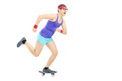 Nerdy grabb som rider en liten skateboard arkivbilder