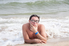 Nerdy guy on the beach Royalty Free Stock Photos