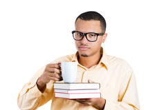 Nerdy guy with a coffee mug in one hand and books in other Stock Images