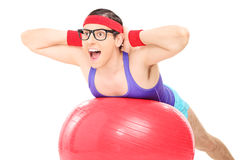 Nerdy guy doing an exercise on a pilates ball Royalty Free Stock Photography
