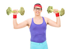 Nerdy guy exercising with two broccoli dumbbells Royalty Free Stock Images