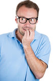Nerdy guy with glasses biting his nails and looking to the side with a craving for something or anxious Royalty Free Stock Photo