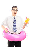 Nerdy guy holding a pink swimming ring and cocktail Royalty Free Stock Photo