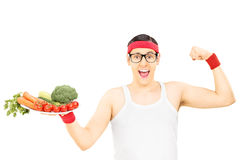 Nerdy guy holding plate with vegetables and showing muscle Stock Photography