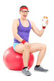Nerdy guy sitting on fitness ball and holding milk bottle Stock Photography