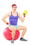 Nerdy guy sitting on pilates ball and lifting a dumbbell Royalty Free Stock Photo