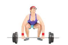 Nerdy guy struggling to lift a barbell Royalty Free Stock Image