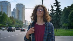Nerdy handsome man in glasses with curly hair checking on phone and waiting for taxi, holding smartphone in hand and stock video footage