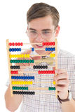 Nerdy hipster adding on abacus Stock Images