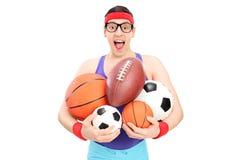 Nerdy Kerl, der ein Bündel Sportbälle hält lizenzfreies stockfoto