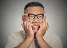 Nerdy Kerl des Headshot mit Gläsern seine Nägel beißend, die besorgtes heftiges Verlangen schauen Stockfotografie