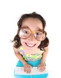 Nerdy Kind unter Verwendung des Computers, der oben lächelnd schaut Stockbild